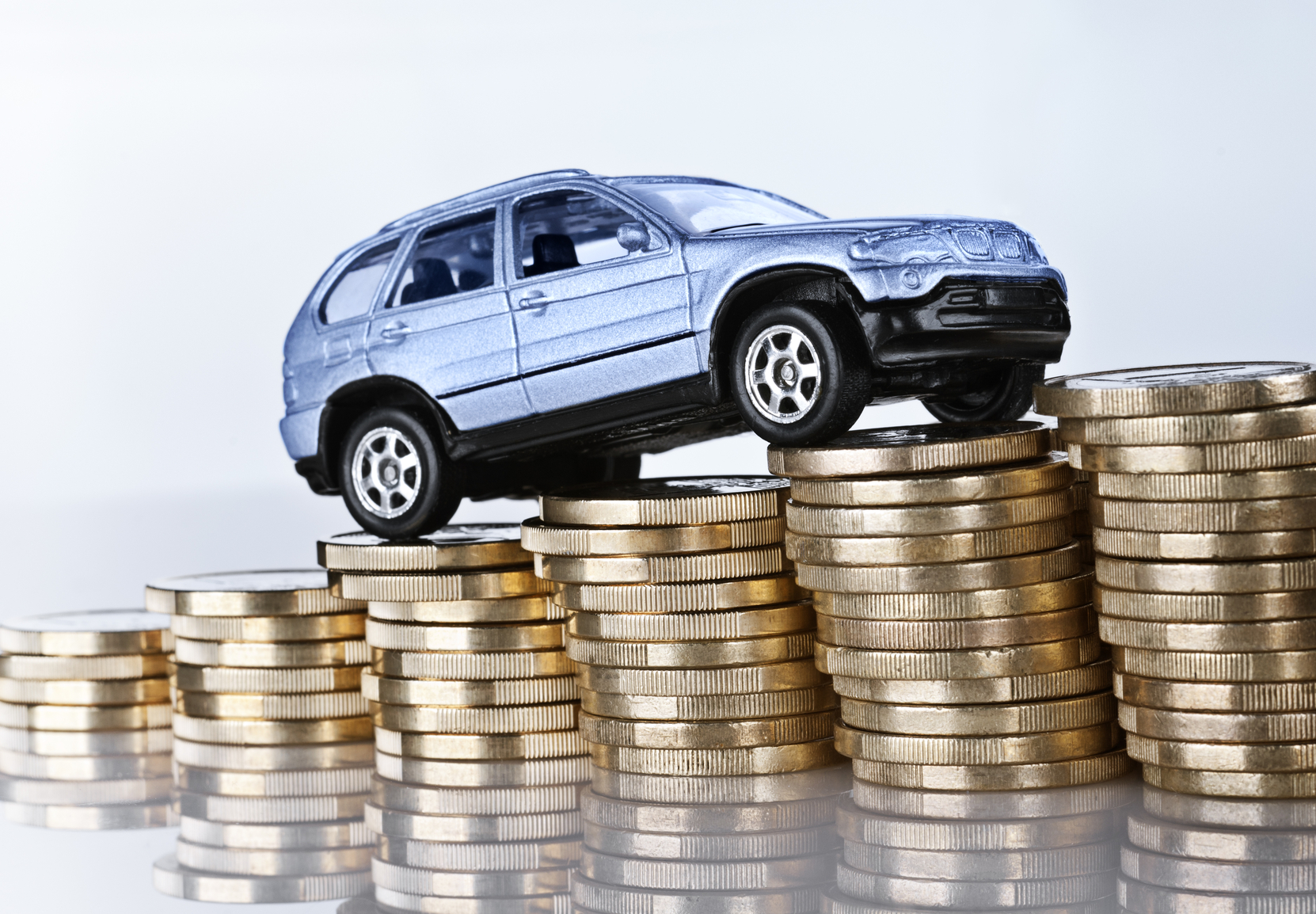"""Frankfurt, Hessen, Germany - April 04, 2012: Car drives up a ramp made from coins."""